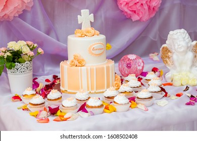 Cake with mastic cross for christening child party. Baptism candy bar, angel statue, cupcakes and flower petals on the table. Inscription on cake - name Ekaterina in Russian