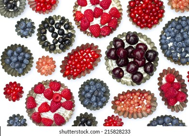 Cake molds with fresh fruit, strawberry ,currant, bleu berry, white berry, raspberry on a white background.