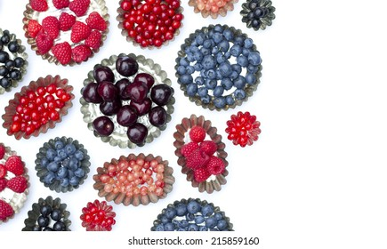 Cake molds with fresh fruit,strawberry, currant, blueberry raspberry ,cherry,white berry on a white background. Space to right on.