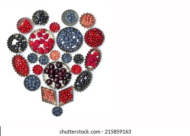 Cake molds with fresh fruit,strawberry, currant, blueberry raspberry ,cherry,white berry on a white background. Shape of a heart,
