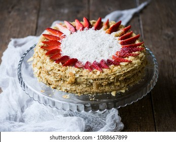 Cake Napoleon decorated with strawberries on an old wooden background with white fabric