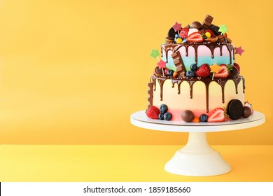 Cake on birthday with colorful rainbow cream on a yellow background decorated with berries, colorful sprinkles, poured with chocolate.