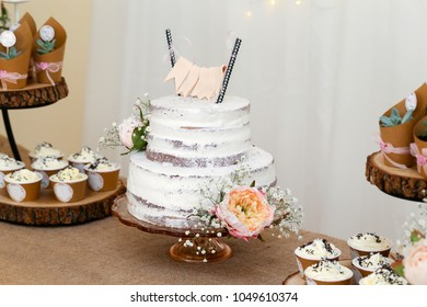Cake on a party table with flowers and cupcakes