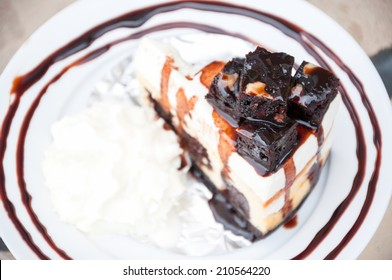 Cake on a plate and topped with chocolate.