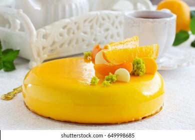 Cake with orange mousse and almond krokantom in the mirror glaze. Selective focus.