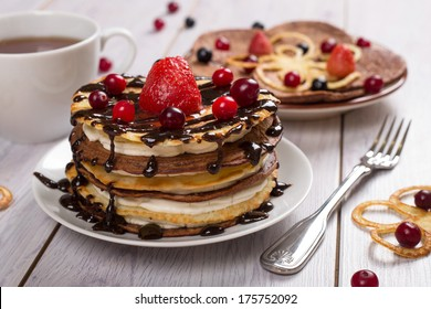 Cake of pancakes with fresh berries and chocolate