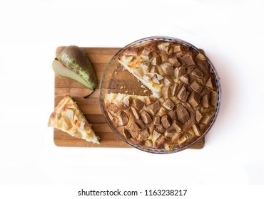 Cake piled cinnamon top view with pear on a wooden board on a white background. Next to the piece of pie and a cut pear