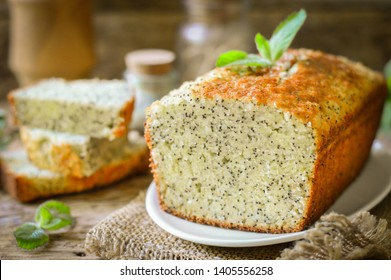Cake with poppy seeds, decorated with a sprig of mint. Wooden background