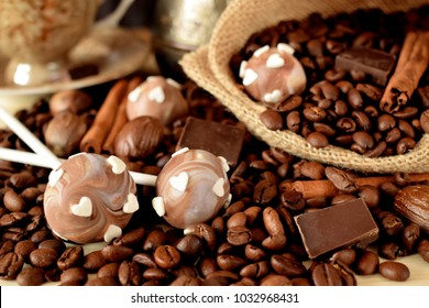 Cake pops with coffee glazing, coffee beans, chocolate pieces and cinnamon sticks