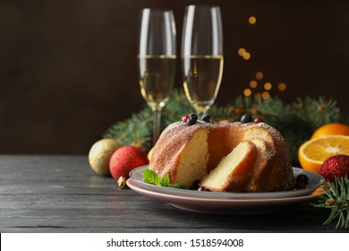 Cake with powdered sugar, berries and mint on wooden background, copy space