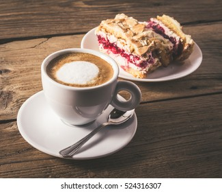 cake with raspberries and cup of coffee on a wooden table