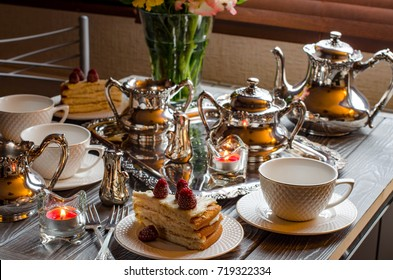Cake with raspberries. Festive table with beautiful dishes, desserts, candles, flowers in a vase. 5 o'clock tea. Silverware to serving. Selective focus. Festive background.