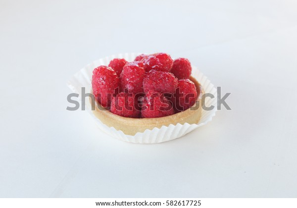 cake with raspberries on white table