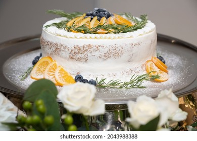 スライスしたオレンジとブルーベリーの山を持つケーキ