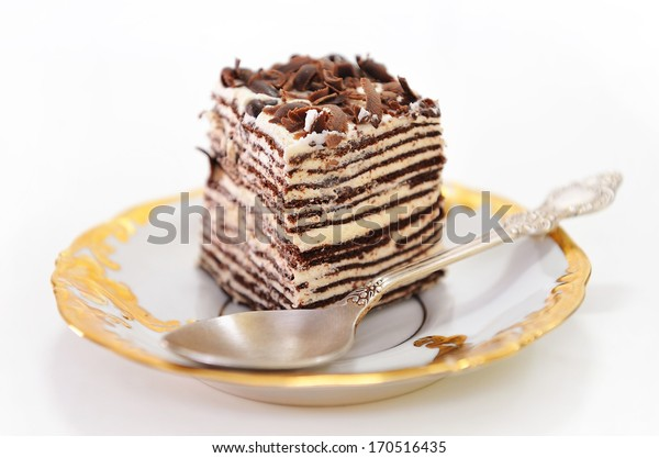 Cake with spoon on golden saucer.