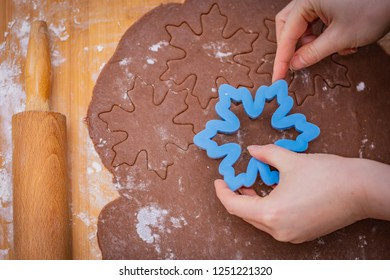 Cake spread on a countertop with starred hands, hands hold the form, the rolling pin lies on the edge
