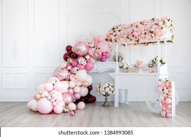 Cake stand with pink cake flowerpots, geometric flower holder, cup cakes, and balloon cascade