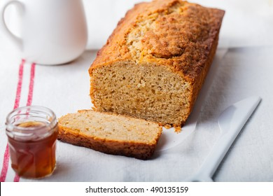 Cake, tea loaf with jam and cream on a textile white background. Rustic style.