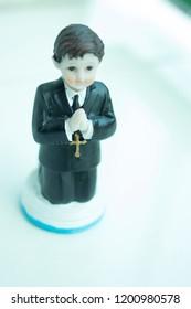 Cake topper Catholic holy communion ceremony religious boy praying to Christian God in church.
