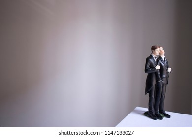 Cake topper gay wedding couple of two male grooms holding romantic marriage embrace of LGBT love.