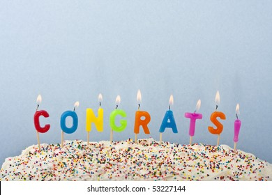 a cake with white frosting and sprinkles decorated with candles spelling out congrats