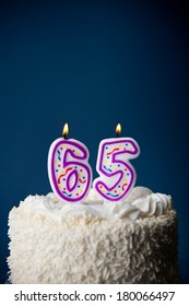 Cake: White Iced Birthday Cake With Candles For 65th Birthday