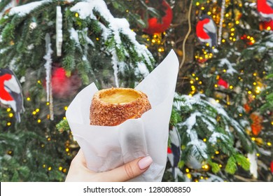 Trdelnik(spit cake) in woman's hand made from rolled dough that is wrapped around a stick, then grilled and topped with sugar and walnut mix.