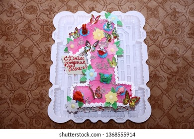 Cake.Festive delicious pink cake. With inscription in Russian happy birthday Ksenia. Decorated with different figurine cream figures.