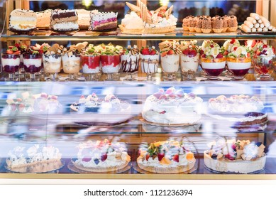 Cakes in the bakery window. Rich variety of chocolates and candies in display window of pastry shop. Cookies showcase.