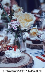 cakes decorated with cream and berries stand on a wooden table next to flowers