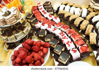 Cakes and fruits at dessert table at reception
