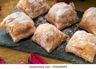 Cakes with icing sugar on black slate plate