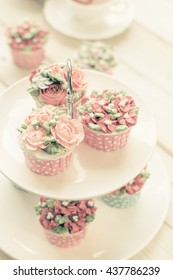 cakes and macaroons on two tiered tray with teapot and cup background. Afternoon tea