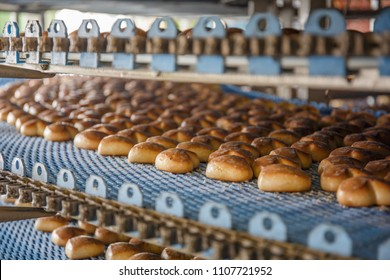 Cakes on automated round conveyor machine in bakery food factory, production line close up