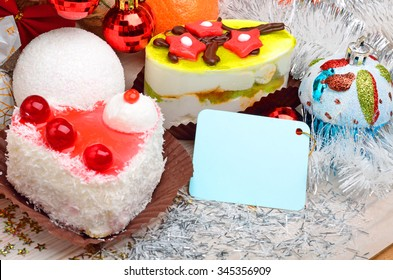 Cakes on christmas background with snow, cofetti, card for text