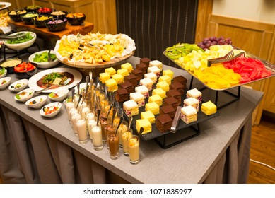cakes and cakes on a tray with fruit cut slices for a buffet table