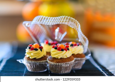 Cakes in a plastic disposable container on a colored background