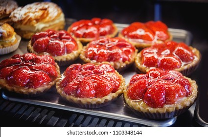 Cakes with strawberries on a metal tray. Close up.