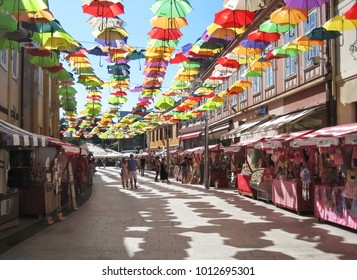 Cakovec, Croatia - July 30, 2016 : Couple;man and wife walking on the empty promenade of city Cakovec in shade with colorful umbrellas above them|fest|porcijunkulovo|hot summer day
