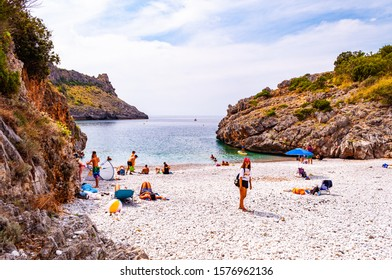 Cala Bianca, Italy - September 06, 2019: People resting on amazing Cala Bianca beach surrounded by rocks and Tyrrhenian sea bay with crystal clear deep water full of underwater life