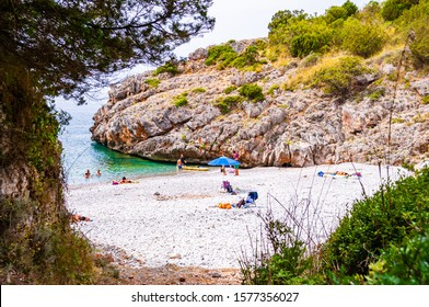 Cala Bianca, Italy - September 06, 2019: One of a couple secret entrances to amazing Cala Bianca beach surrounded by rocks and Tyrrhenian sea bay with crystal clear deep water full of underwater life