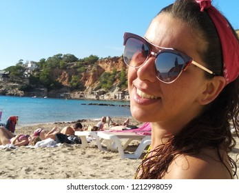 Cala d'Hort, Ibiza / Spain - October 10 2018 : girl in summer outfit enjoys the warmth of the sun's rays