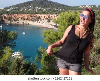 Cala D'hort, Ibiza / Spain - October 10 2018 : a girl enjoys the ibizenca holiday by making the tourist in cala d'hort, in front of the magical island of es vedra.