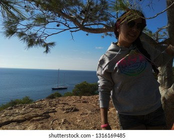 Cala D'Hort, Ibiza / Spain - September 23 2018 : young caucasian woman. panorama of cala d'hort in front of the island of Es Vedra