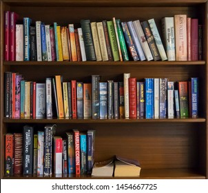 CALA D'OR, MALLORCA, BALEARIC ISLANDS, SPAIN - JUNE, 2019: Brown wooden bookshelf with many fiction books in hotel librar.