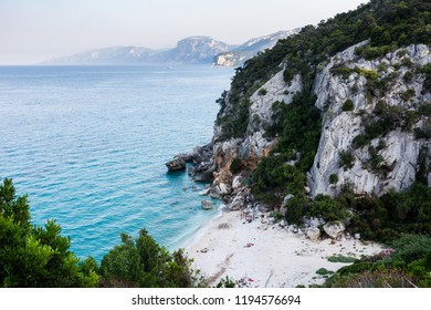 Cala Gonone beach with the majestic Tyrrhenian sea in Sardinia with unrecognizable people on an overcast summer day, perfect vacation place. Seascape view.