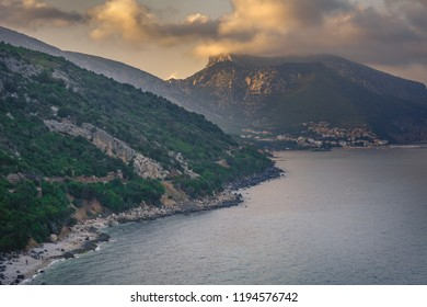 Cala Gonone beach with the majestic Tyrrhenian sea in Sardinia with branch in foreground on an overcast summer day, perfect vacation place. Seascape view golden hour.