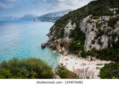 Cala Gonone beach in Sardinia with unrecognizable people on an overcast summer day, perfect vacation place. Seascape view.