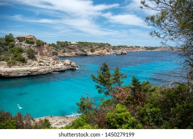 Cala Llombards, Mallorca, Spain, 06/18/2019: Coast of Cala Figuera on a sunny summer day in june. mediterranean sea with turquoise water next to rocky coastline with botany and different plants