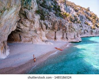 Cala Luna Sardinia, young couple with kayak boat on the beach of Cala Luna Sardinia Italy